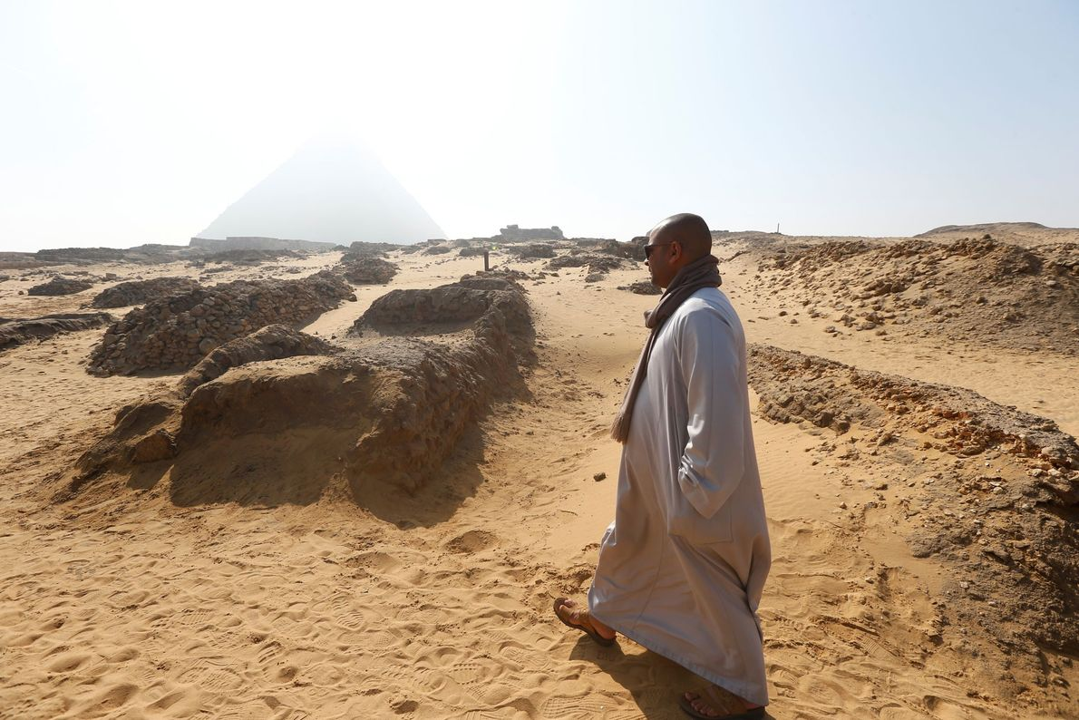 Ein Mann läuft an dem gerade entdeckten Grab auf dem Gizeh-Plateau entlang. Hier ist die Ausgrabungsstätte ...