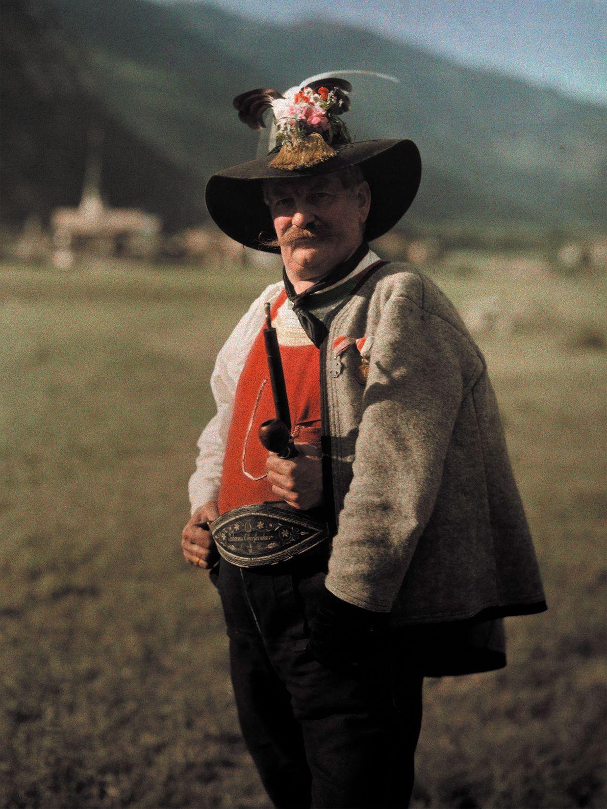 Ein Mann aus dem Zilltertal in Österreich trägt einen kunstvoll gefertigten Hut, der mit Federn, Blumen ...