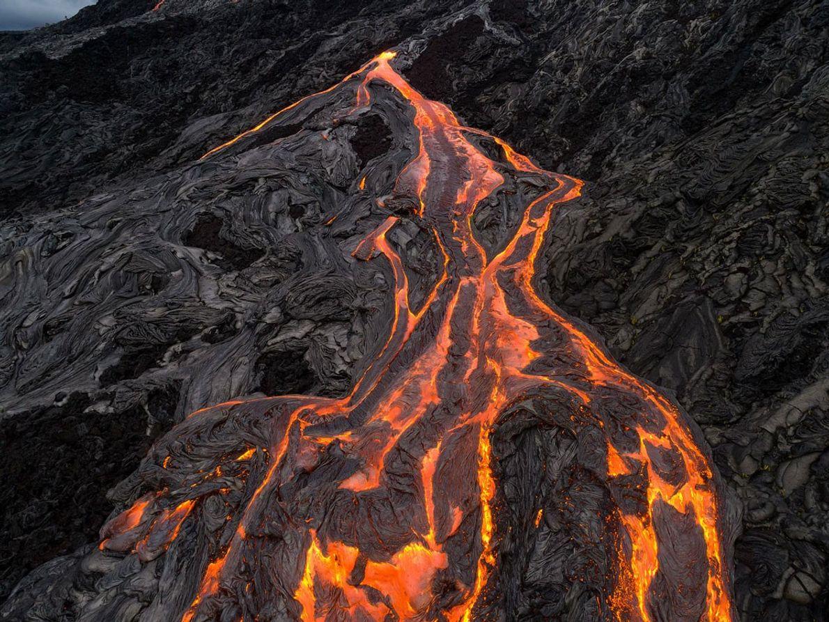 Ein Lavastrom wälzt sich den Berghang hinab.