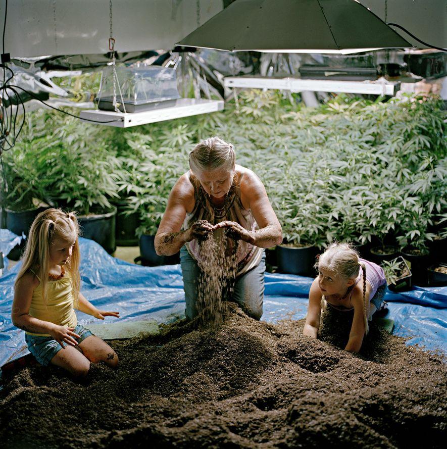 Eine Frau und ihre Enkelinnen bereiten Erde vor.