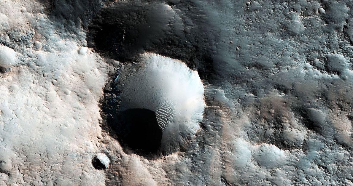Dieses Bild zeigt mehrere Krater auf den mittleren Breitengraden des Mars. Die bläulichen Ablagerungen sind vermutlich …