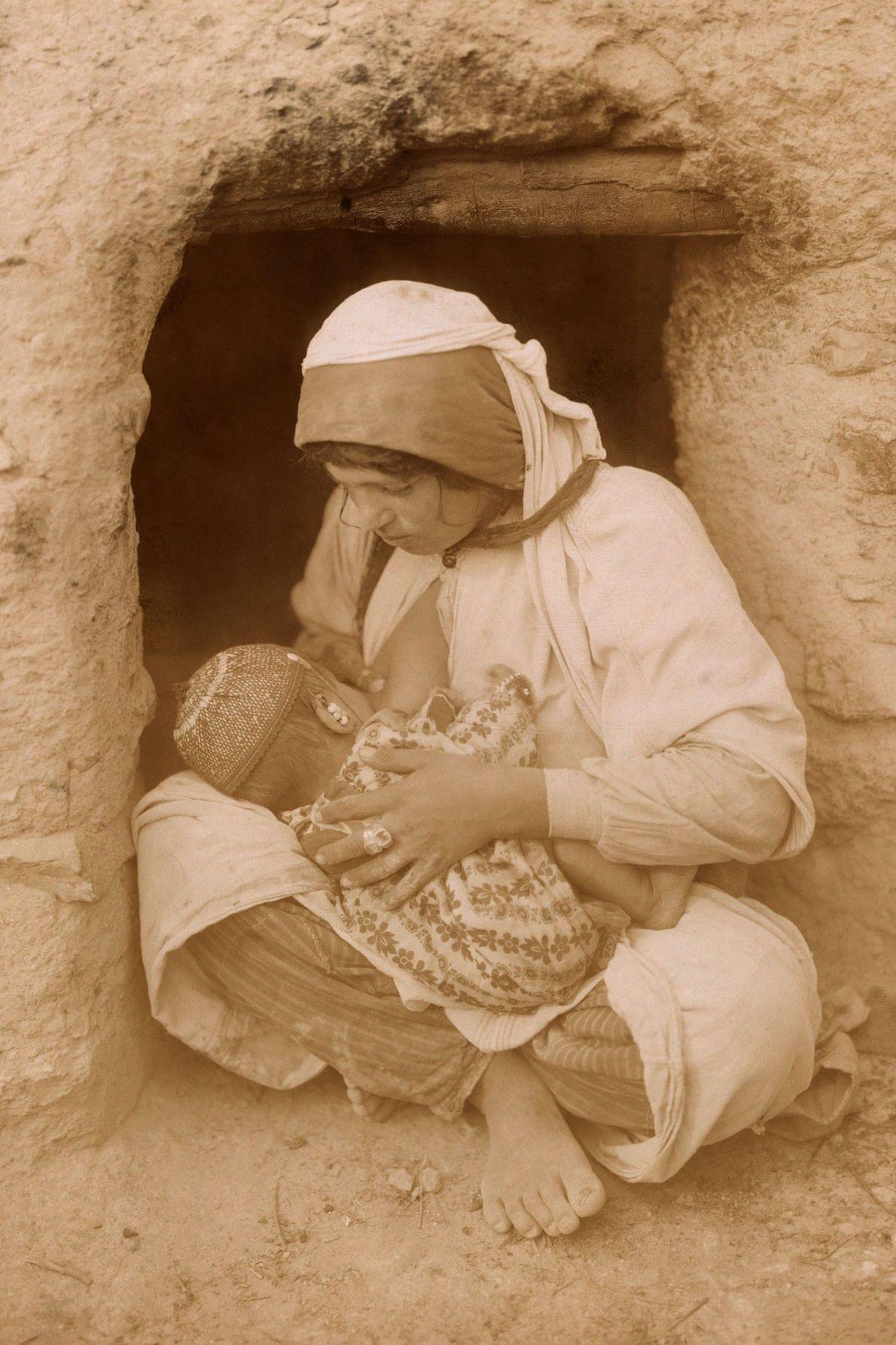 Am Eingang ihres Zuhauses stillt eine Frau im Nahen Osten ihr Kind.