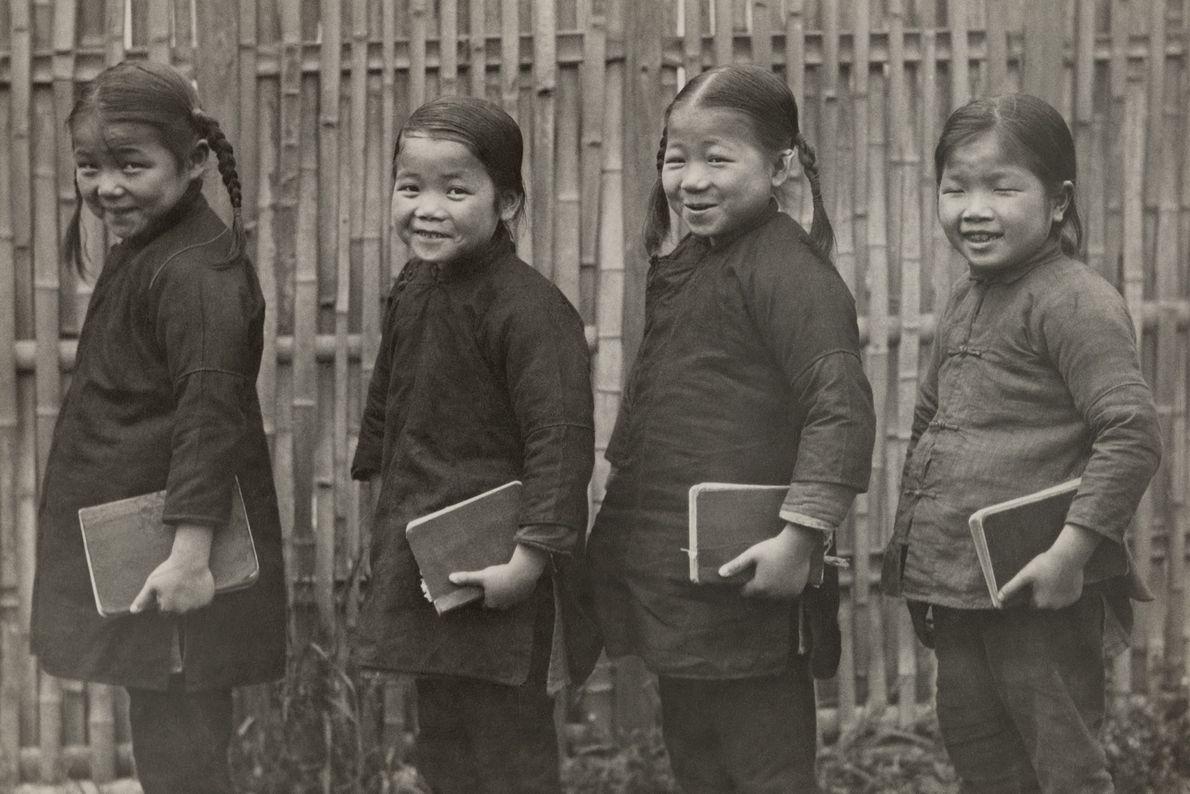 In China machen sich junge Mädchen mit ihren Schulheften auf den Weg in die Schule.