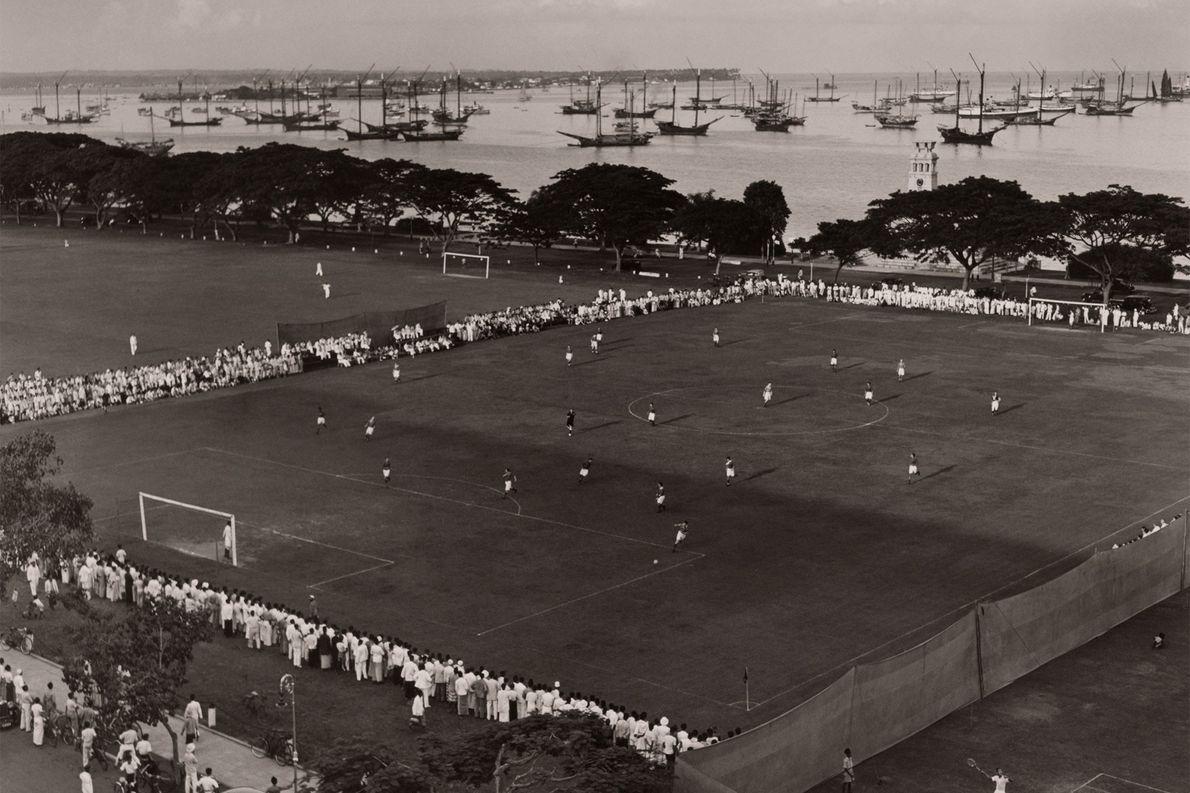 Am Hafen einer Insel im Pazifik versammeln sich Zuschauer um ein Fußballfeld. Die Europäer brachten den ...