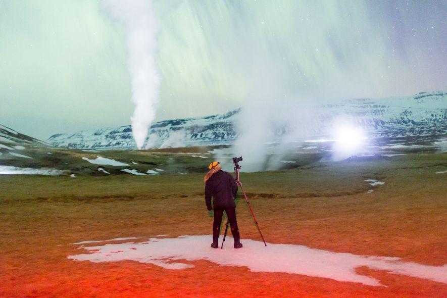Der Dampf aus den geothermalen Spalten hängt wie ein Schleier vor dem Polarlicht am Himmel über ...