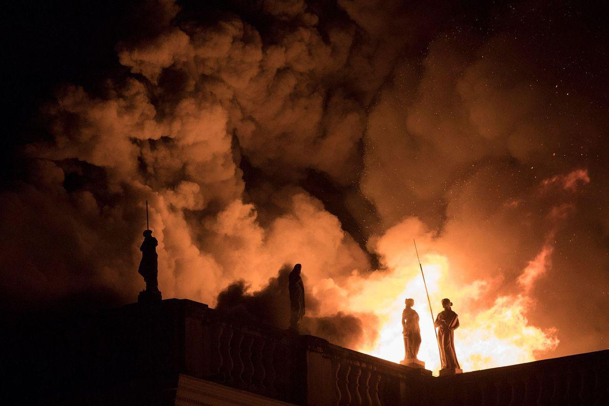 Hinter den Statuen an der Kante schlagen hohe Flammen aus dem Museumsdach. Das Museum gehört zur ...