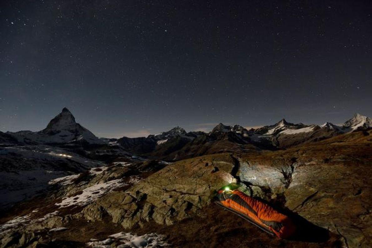 Ein italienischer Wanderer macht es sich in seinem Schlafsack gemütlich, während im Hintergrund das Matterhorn gen …