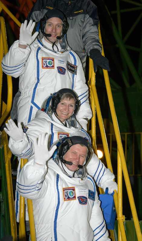 Die Crew winkt zum Abschied, bevor sie die Rakete betritt.