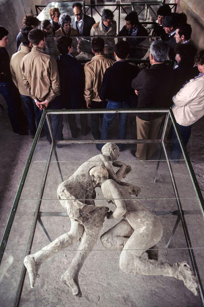 Besucher in den Ruinen von Pompeji sehen sich im Haus des Cryptoporticus die Abgüsse von Opfern ...
