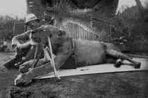 Patterson sitzt neben einem der Löwen