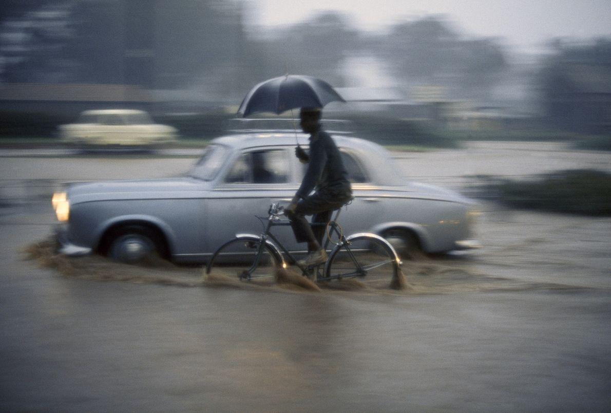 Ein Mann fährt mit dem Rad durch zehn Zentimeter hohes Wasser in Nairobi, Kenia. Das Foto …