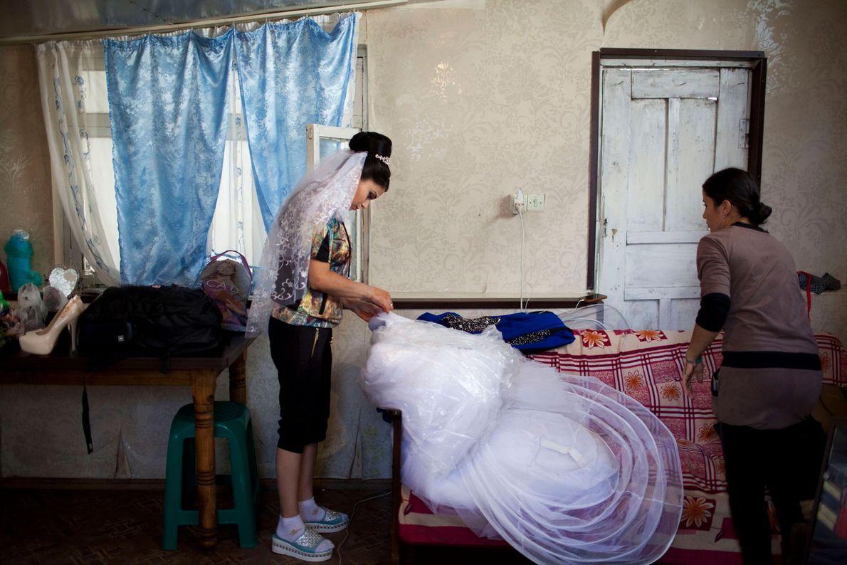 Foto einer jugendlichen Braut, die ihr Hochzeitskleid repariert