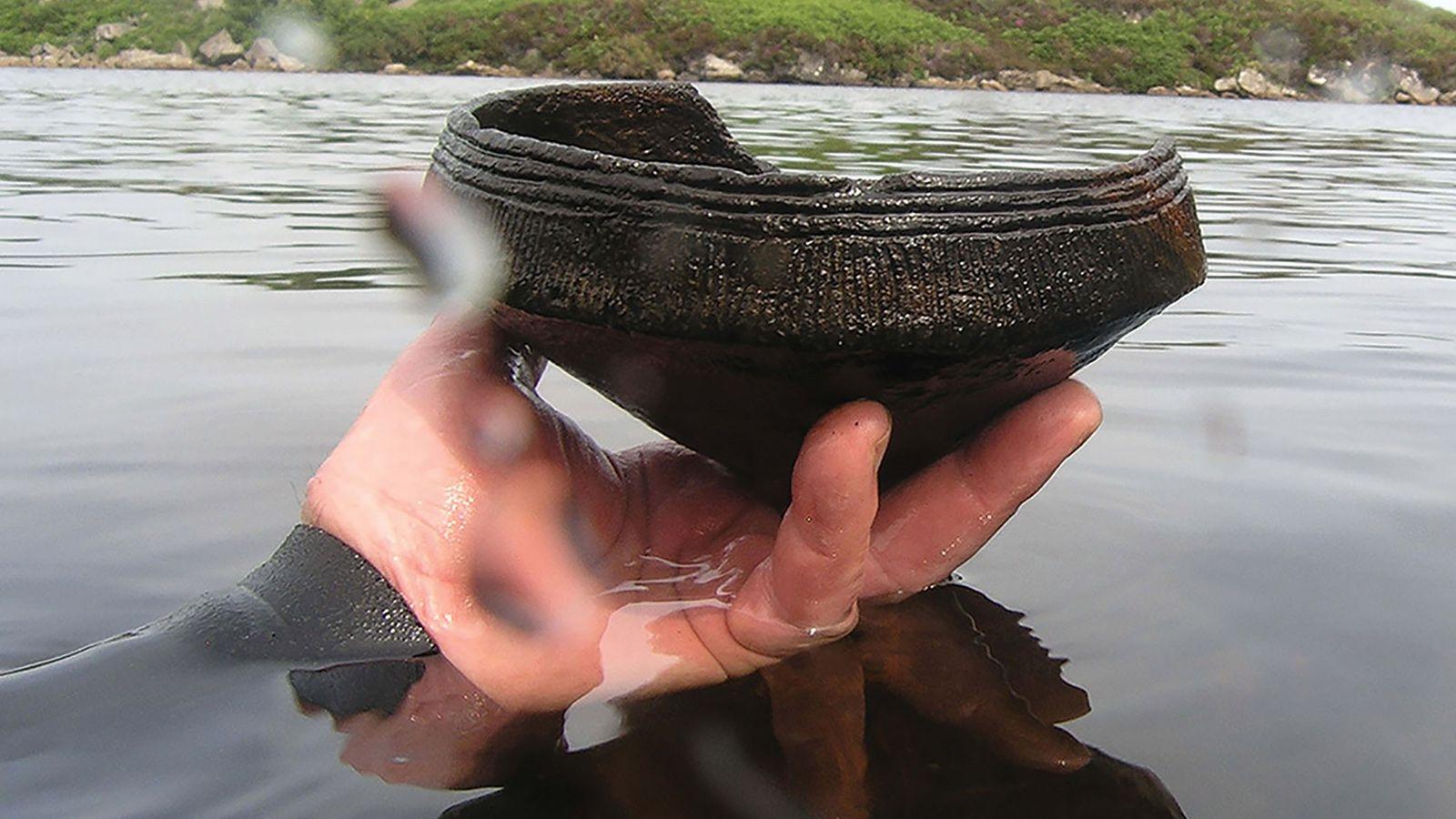 Ein Taucher hält ein neolithisches Keramikgefäß (ca. 3.500 v. Chr.) in der Hand, das er in ...