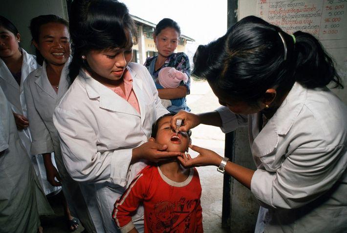 Gesundheitsarbeiter impfen 1991 Kinder im Norden von Laos im Rahmen einer von der UNICEF gesponserten Initiative ...
