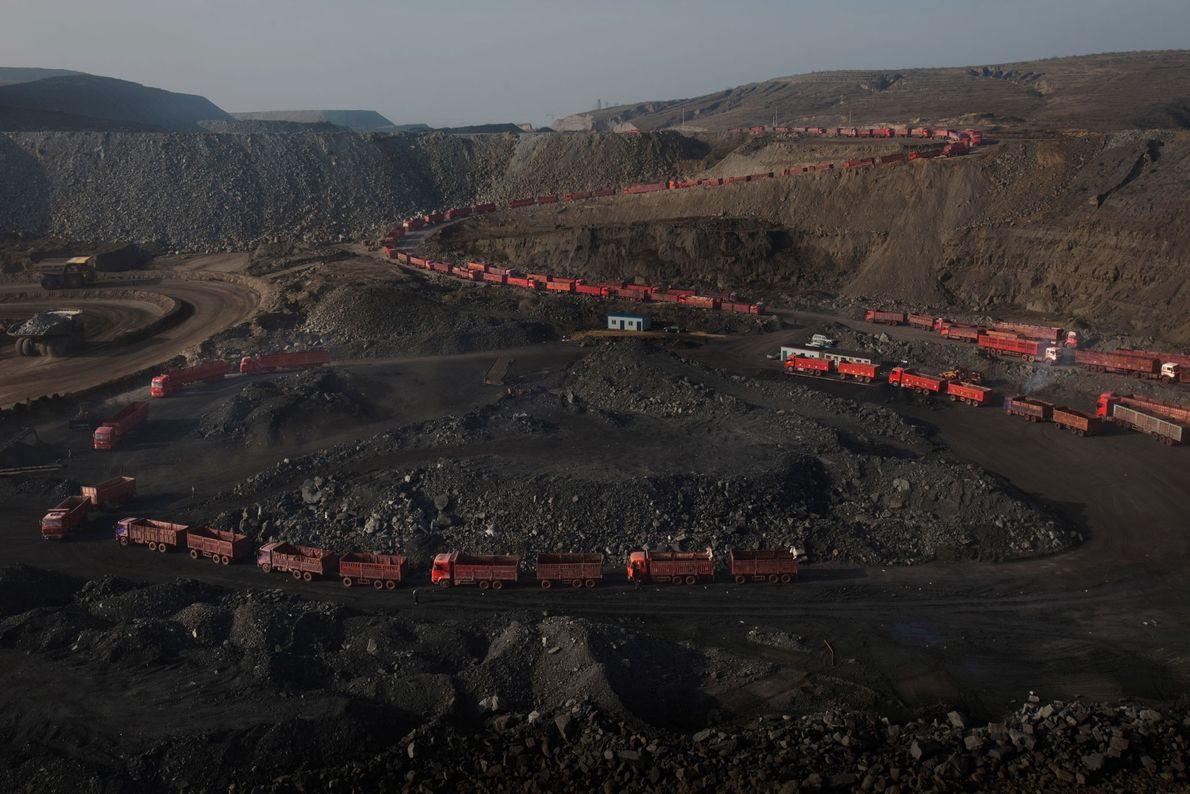 Lkws warten in einer langen Schlange darauf, mit Kohle beladen zu werden.