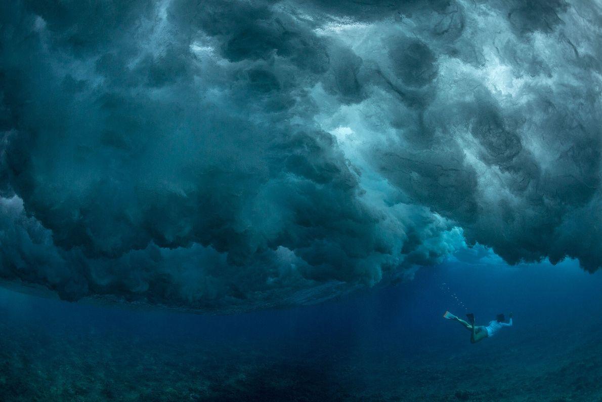 Eine Taucherin wartet im stillen Wasser unter den tosenden Wellen der hawaiianischen Insel Oahu.