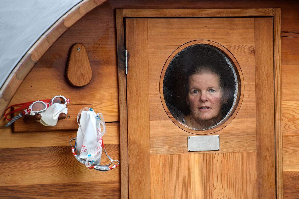 Eine Frau blickt aus dem Fenster einer Sauna, nachdem sie im Brockwell Lido in London schwimmen …