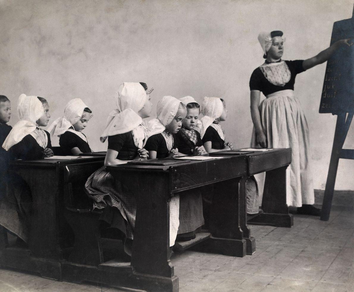 Auf der niederländischen Halbinsel Walcheren besuchen Jungen und Mädchen die Schule. Das Foto erschien 1910 in ...