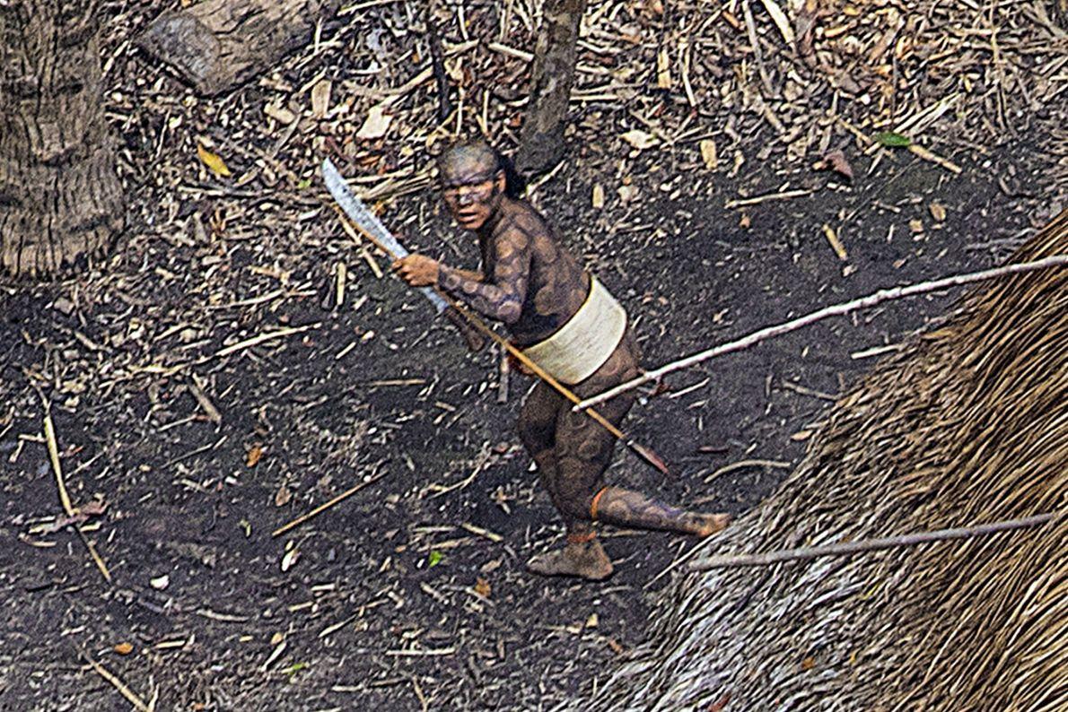 Foto eines Stammesangehörigen mit Körperbemalung, der eine Machete trägt