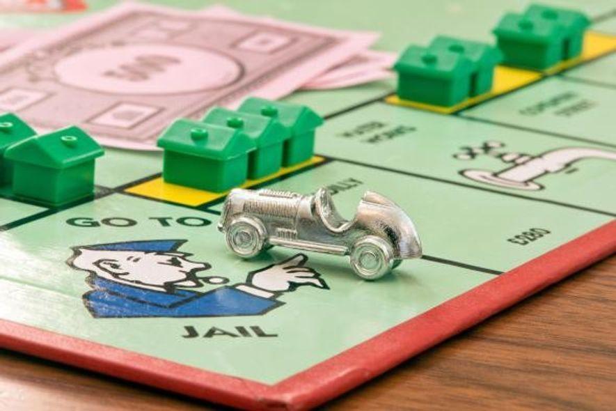 Eine Spielfigur in Form eines Autos auf dem Monopoly-Spielbrett.