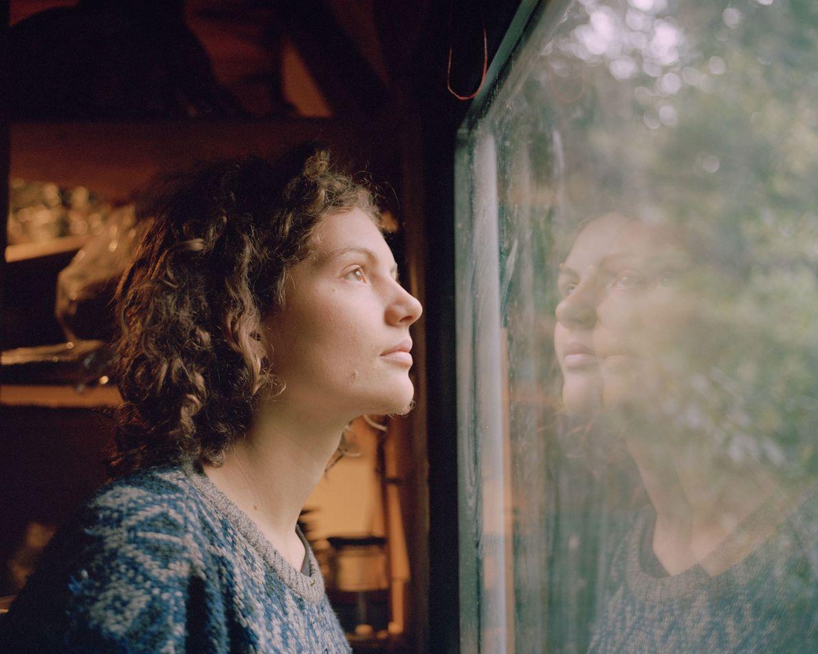 """""""Indigo"""" blickt aus einem Fenster in der Baumhaussiedlung Gallien, der größten im Hambacher Forst."""