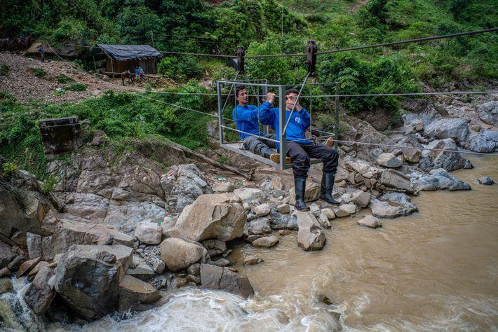"""Zwei Biologen überqueren einen Fluss mit Hilfe von Ziplines – ein """"Arbeitsweg"""", den die lokalen Bauern ..."""