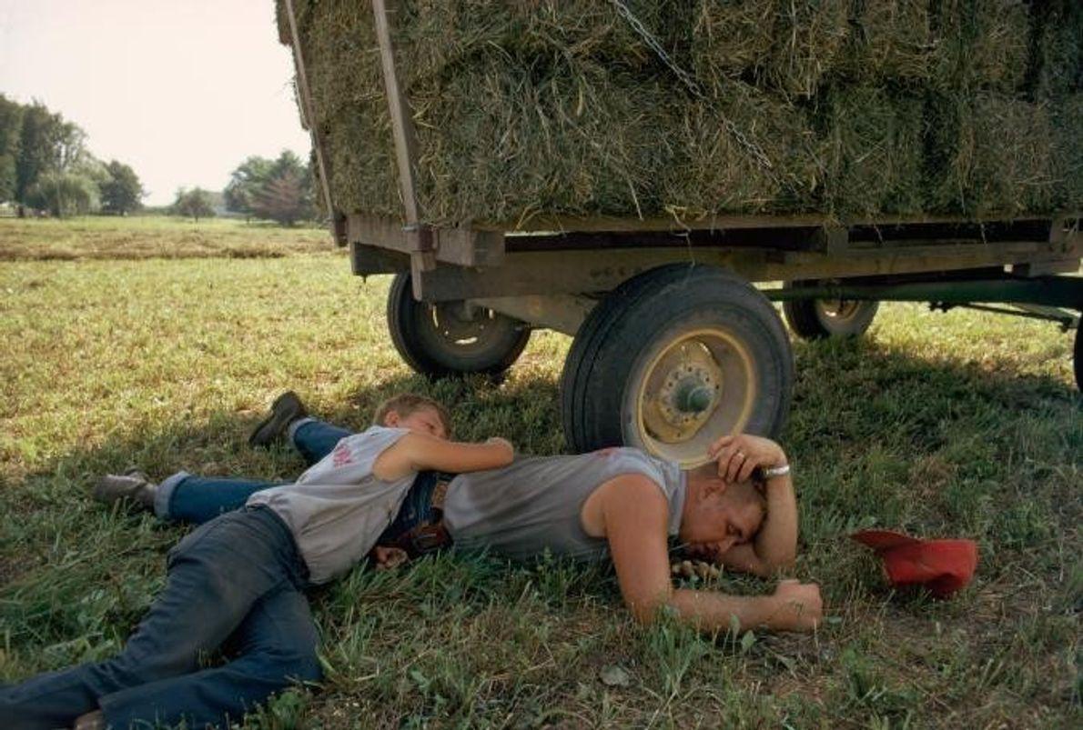 Farmarbeiter in Delaware County in Iowa ruhen sich im Schatten ihres Trucks aus, nachdem sie Heu ...