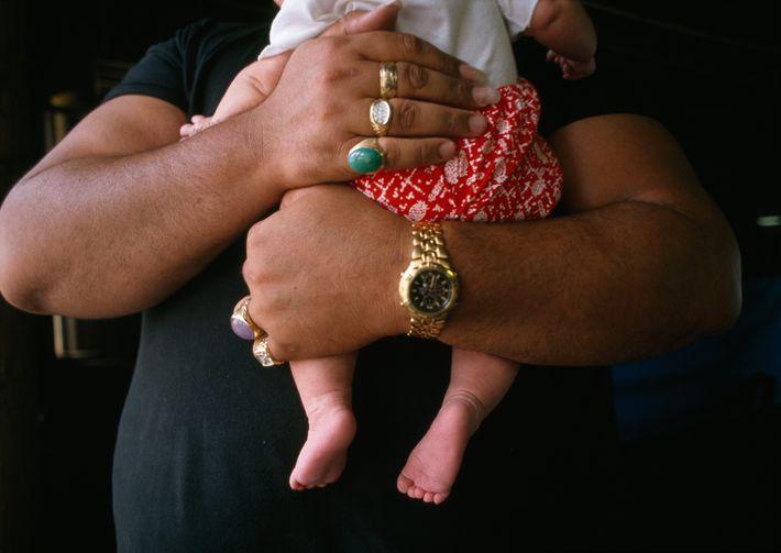 Musiker Kurt Kipapa, Vater von zehn Kindern, hält seinen jüngsten Nachwuchs im Arm.