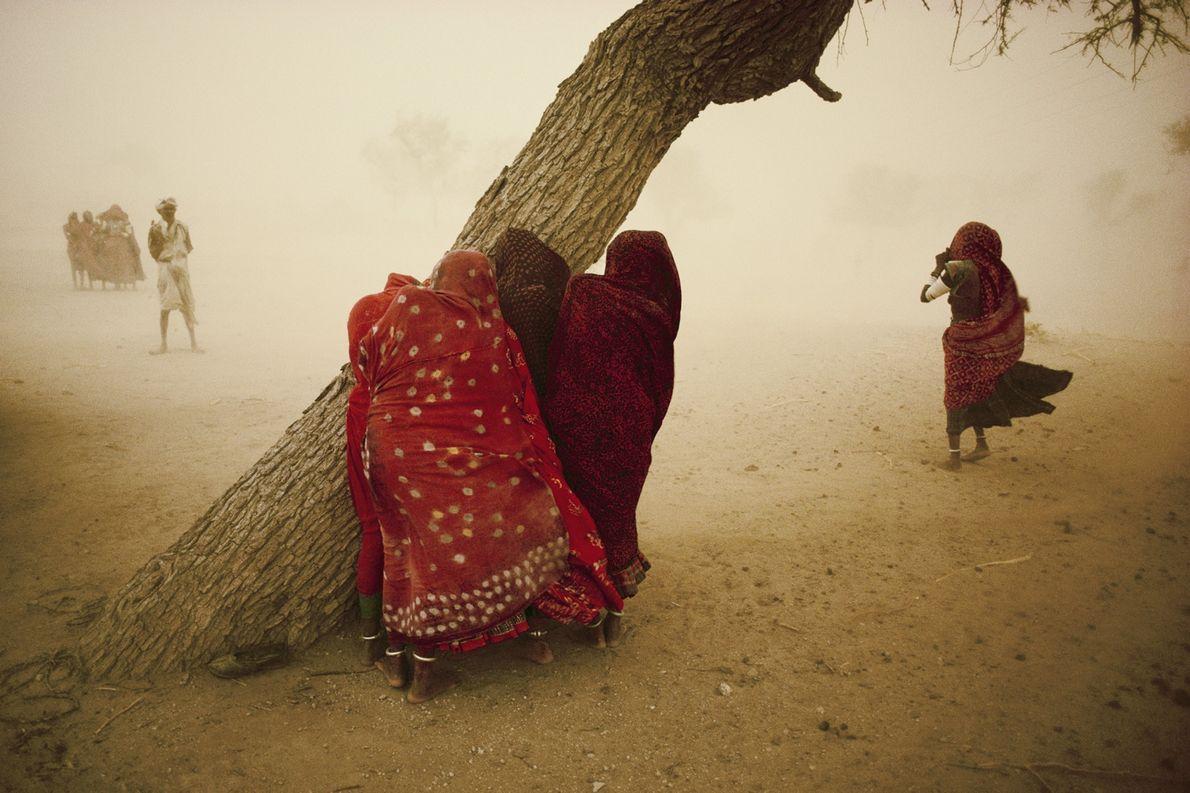Frauen suchen 1984 Deckung vor den starken Winden, die dem Monsun im indischen Rajasthan vorausgehen.
