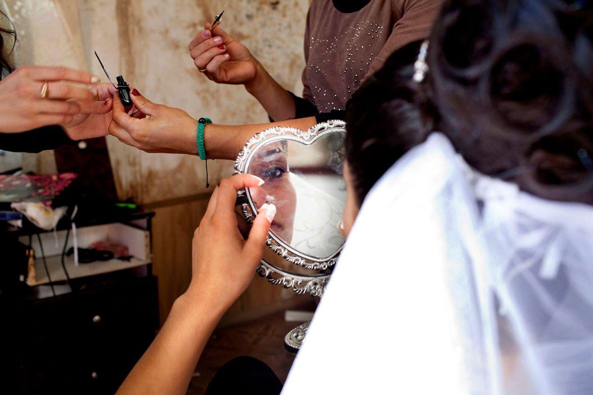 Foto einer jugendlichen Braut, die sich an ihrem Hochzeitstag schminkt