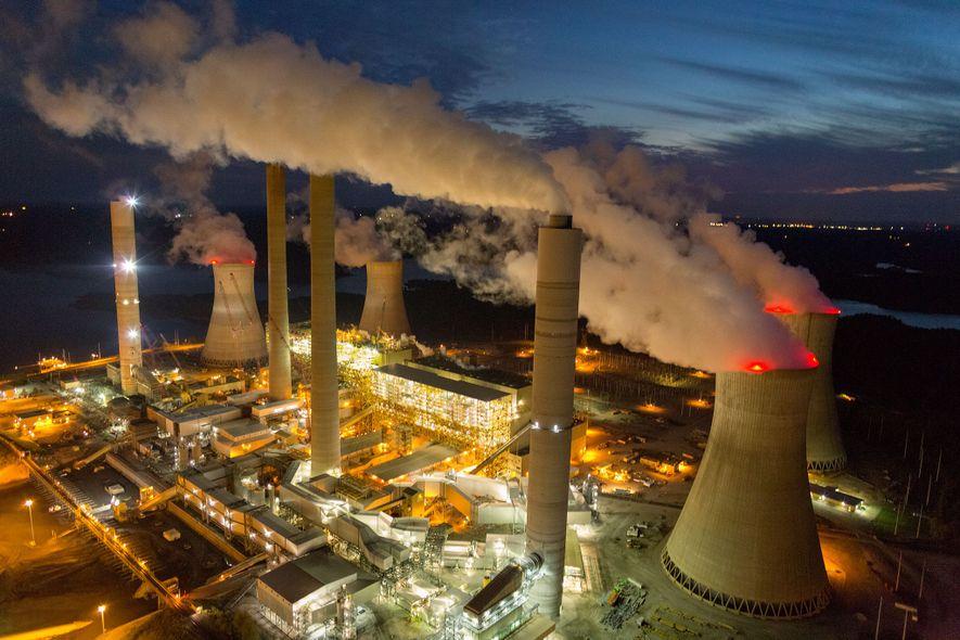 Foto von aufsteigendem Dampf und Rauch aus den Kühltürmen und Schornsteinen eines Kraftwerkes