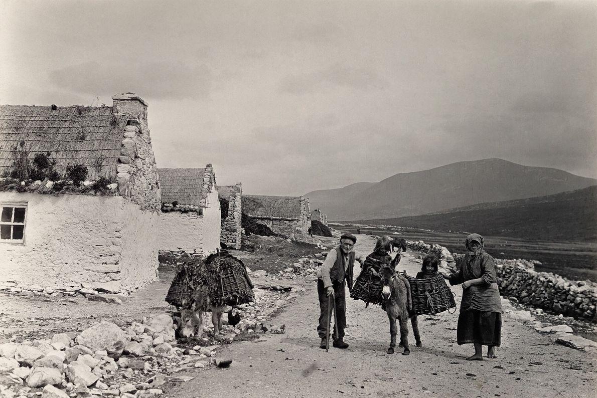 Ein Eselskarren transportiert eine Familie zu einem Dorfmarkt in der Grafschaft Galway, Irland.