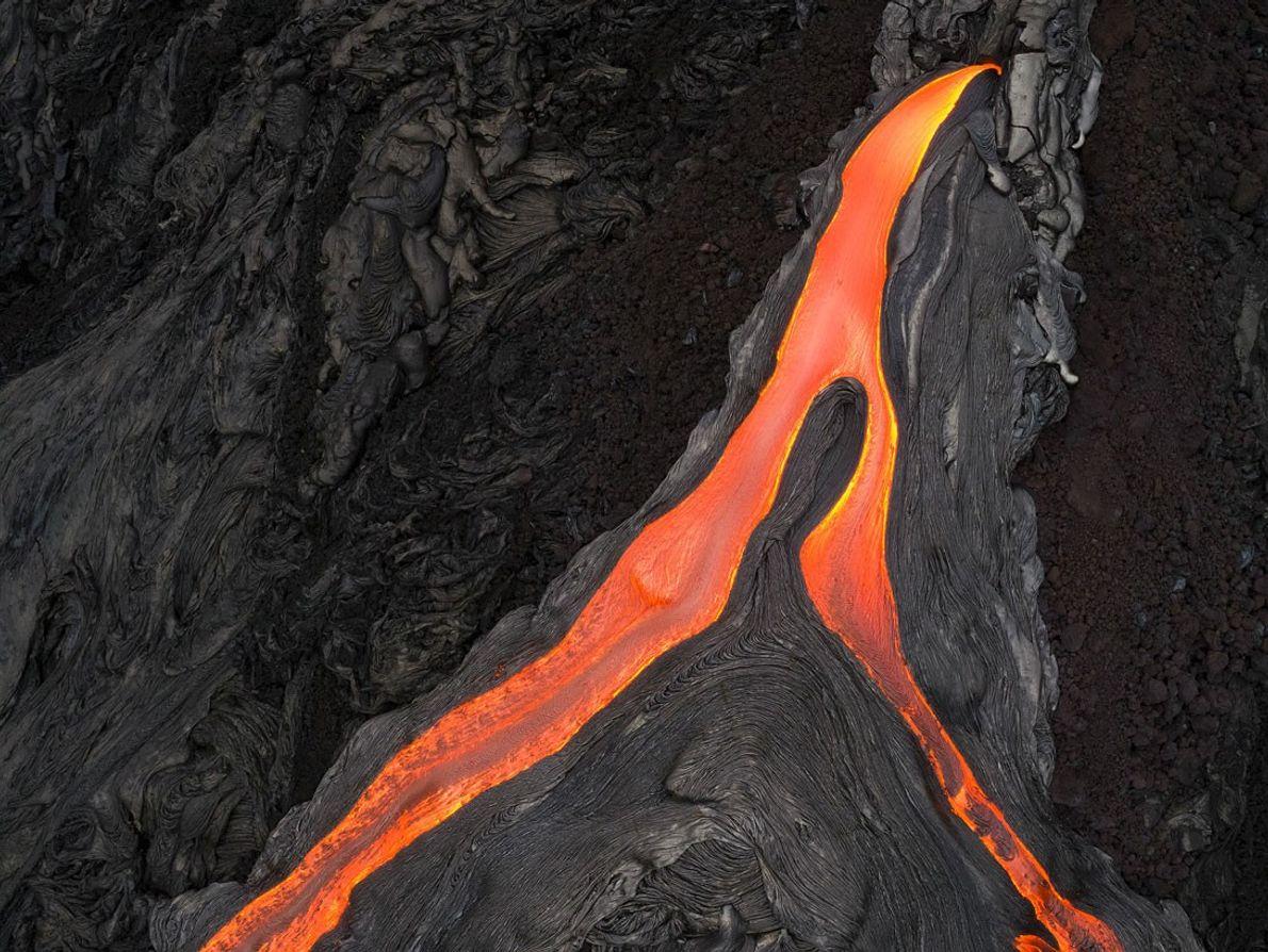 Ein Lavafluss teilt sich und fließt in zwei Armen den Berg hinab.