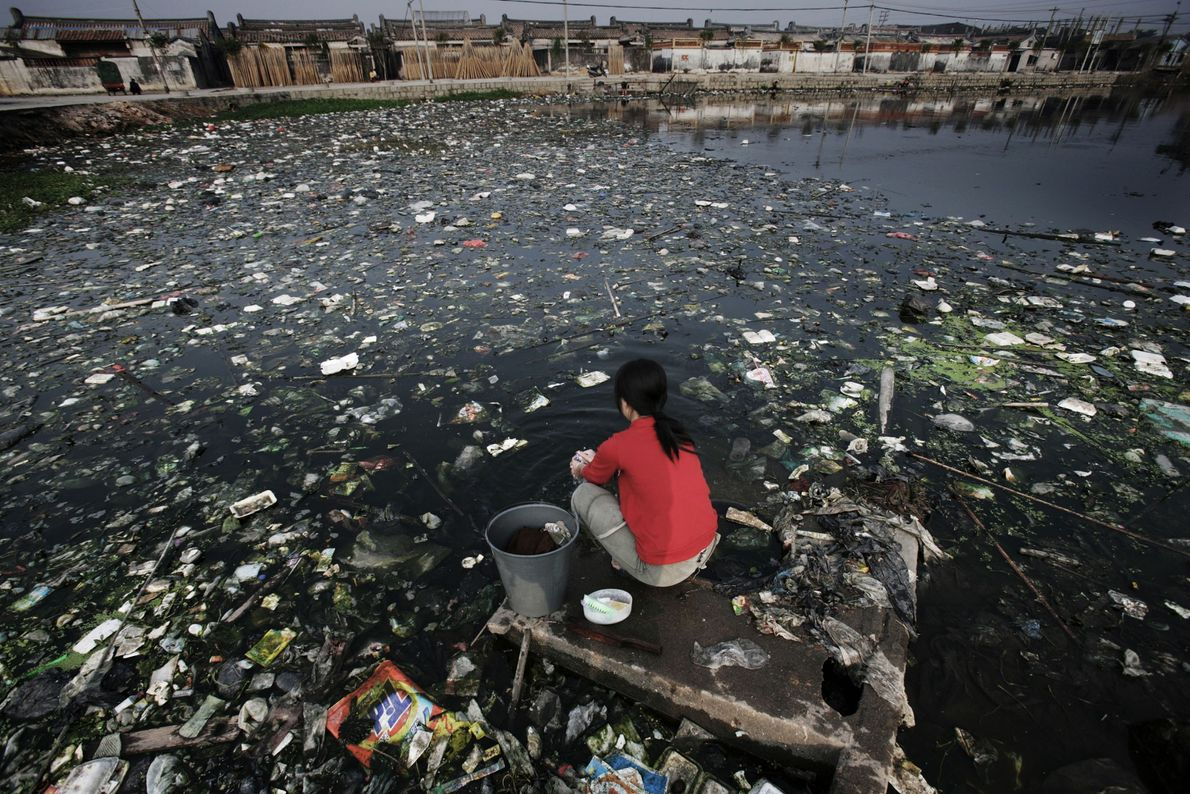 Eine Frau sitzt auf einer kleinen Plattform in einem der am schlimmsten verschmutzten Gewässer in der ...