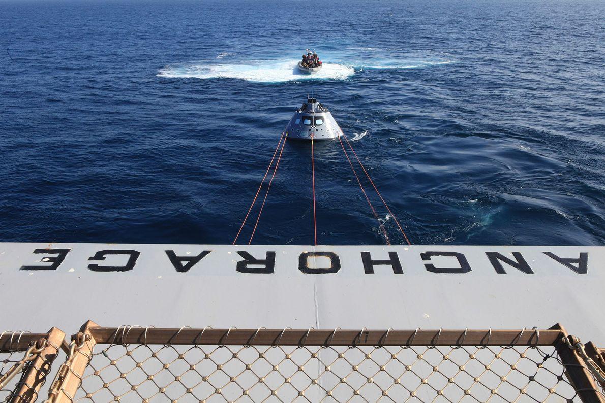 Vom Heck der USS Anchorage aus sieht man die Orion-Testkapsel, die von einer Winde eingeholt wird.