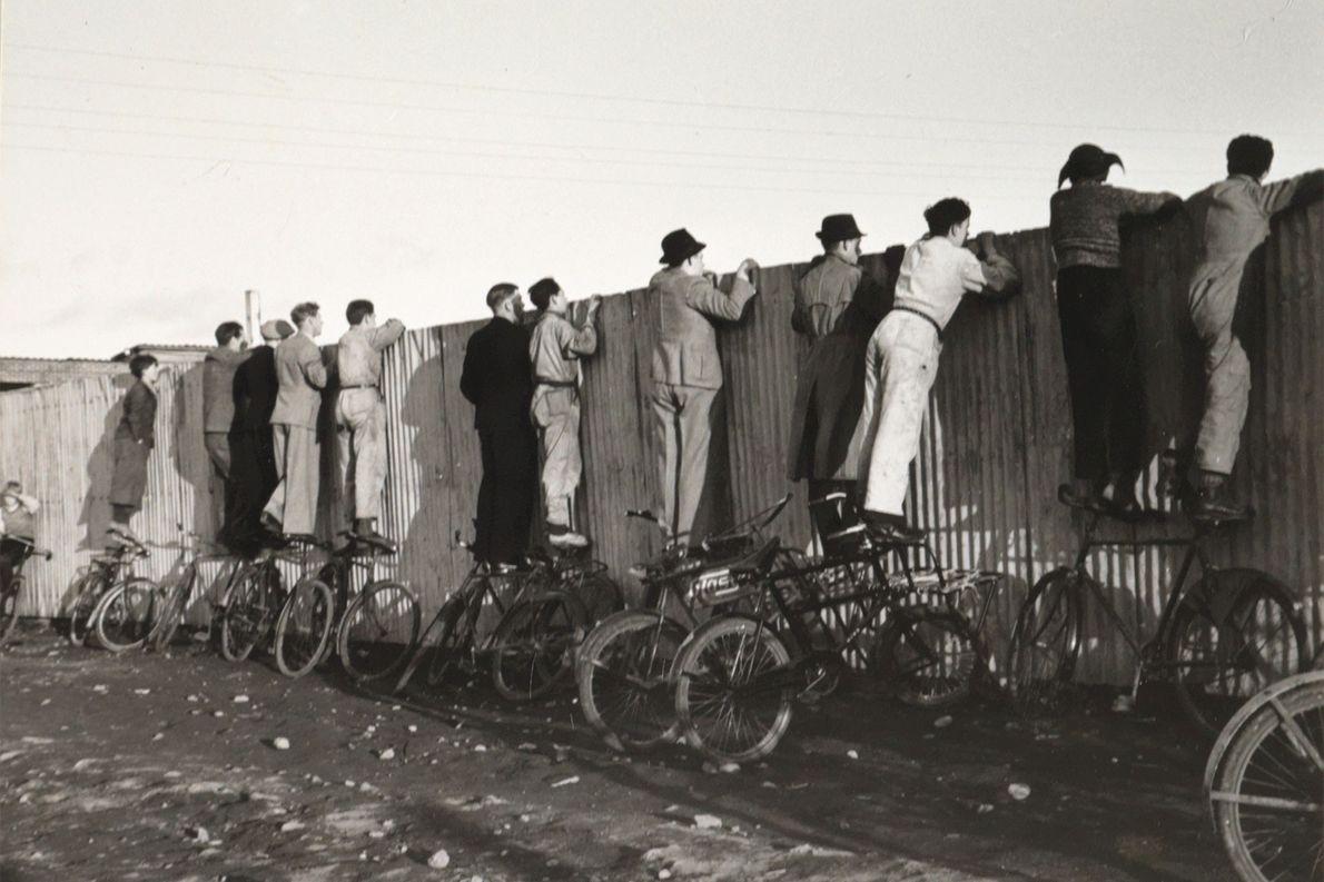 Isländer balancieren 1943 auf Fahrrädern, um über einen Zaun hinweg ein Fußballspiel zu verfolgen.