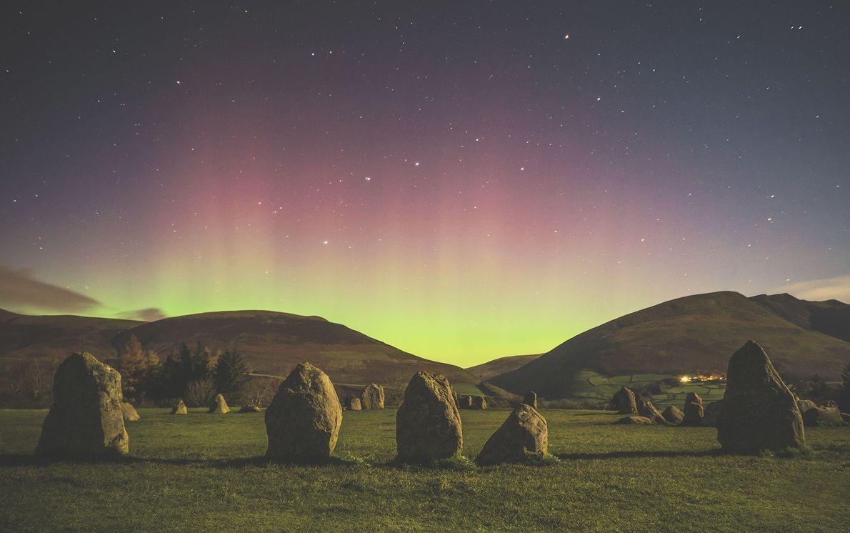 Die Aurora borealis erhellt die Hügellandschaft rund um den Steinkreis in Castlerigg in Cumbria, England.