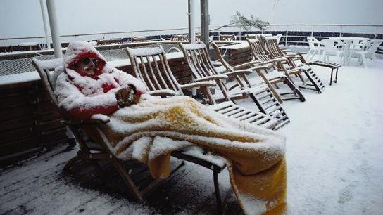 Ein Antarktis-Tourist nahe der Amundsensee schläft an Deck eines Schiffs auf einem Stuhl, während es schneit.
