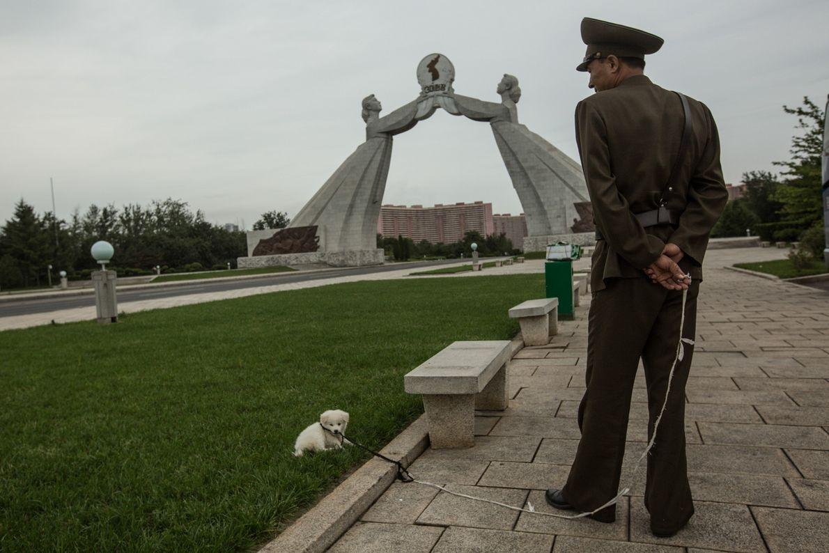 Soldat mit Hund vor Statue