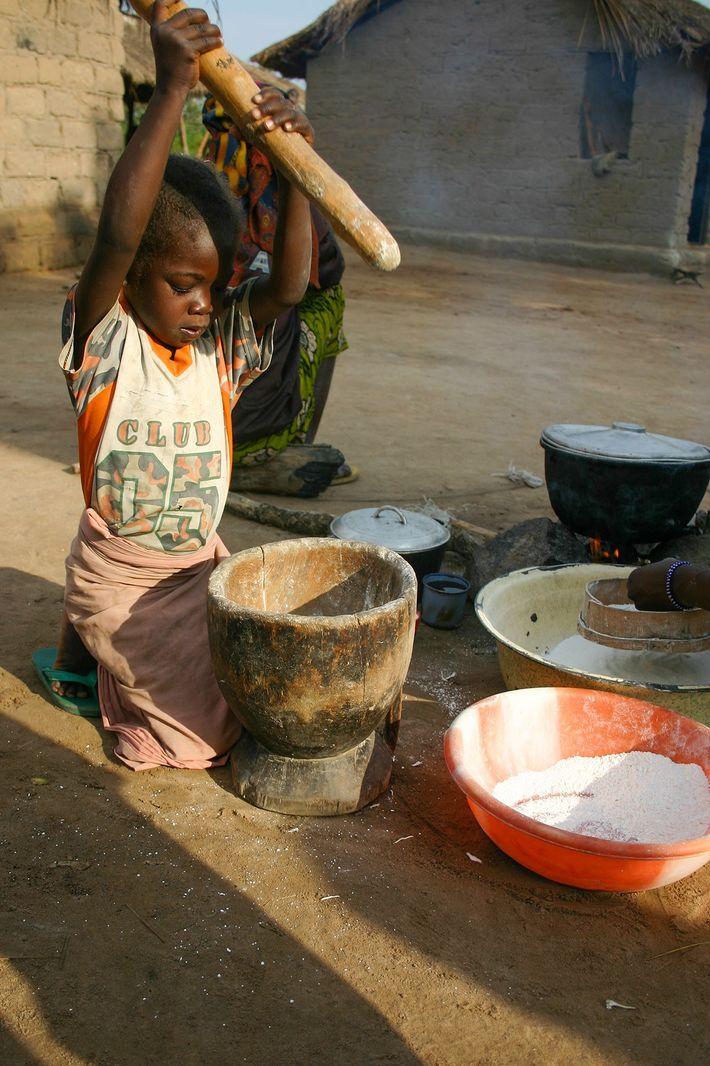 Ein Kind zerstampft Maniok