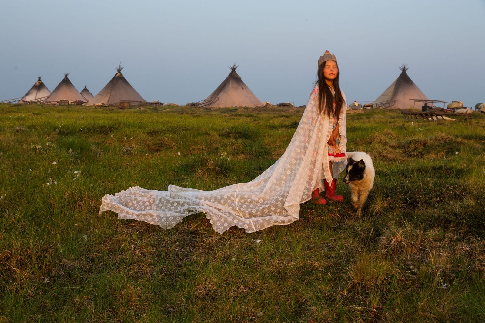 Kristina Khudi trägt einen Vorhang und eine Krone aus Karton und wird so in einem Lager ...