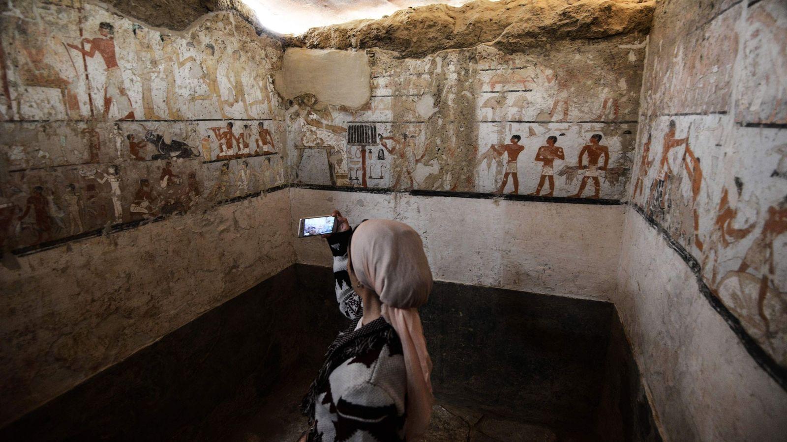 Eine Frau macht im Inneren des Grabes einer Priesterin des Alten Reichs ein Foto. Es befindet ...