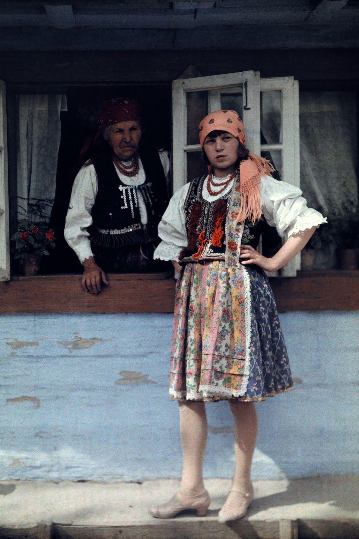 Während ihre Enkelin im polnischen Bronowice 1930 für ein Foto posiert, lehnt sich eine Oma neben ...