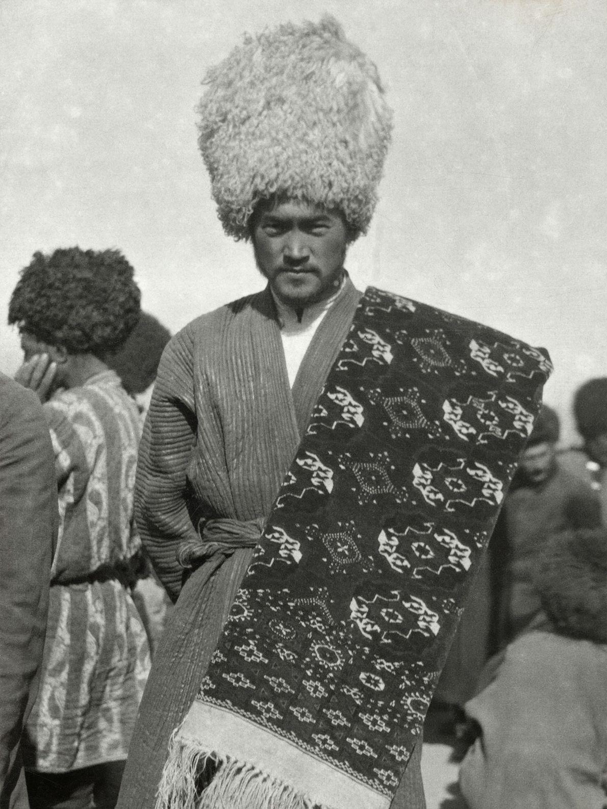 Ein Teppichhändler aus Turkmenistan trägt im frühen 20. Jahrhundert einen Telpek aus Wolle auf dem Kopf. ...