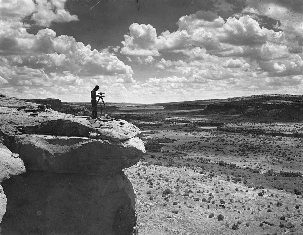 Ein Landvermesser verschafft sich auf einer Klippe einen Überblick über den Chaco-Canyon.