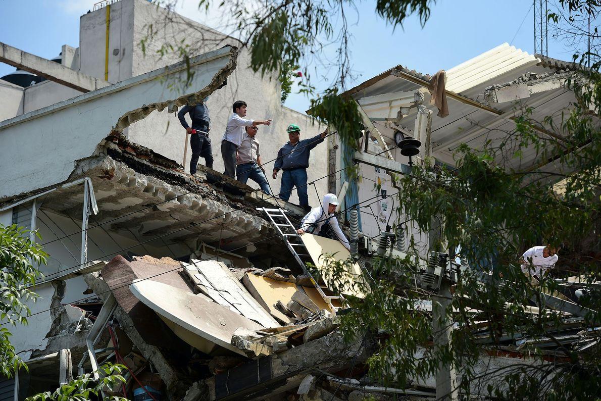 Arbeiter entfernen Trümmer von einem mehrstöckigen Gebäude.
