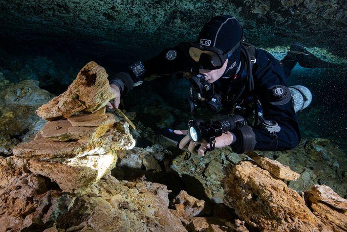 Ein Taucher sammelt Holzkohle aus Feuerstellen, die einst bei der Arbeit der Bergleute die Höhle von ...