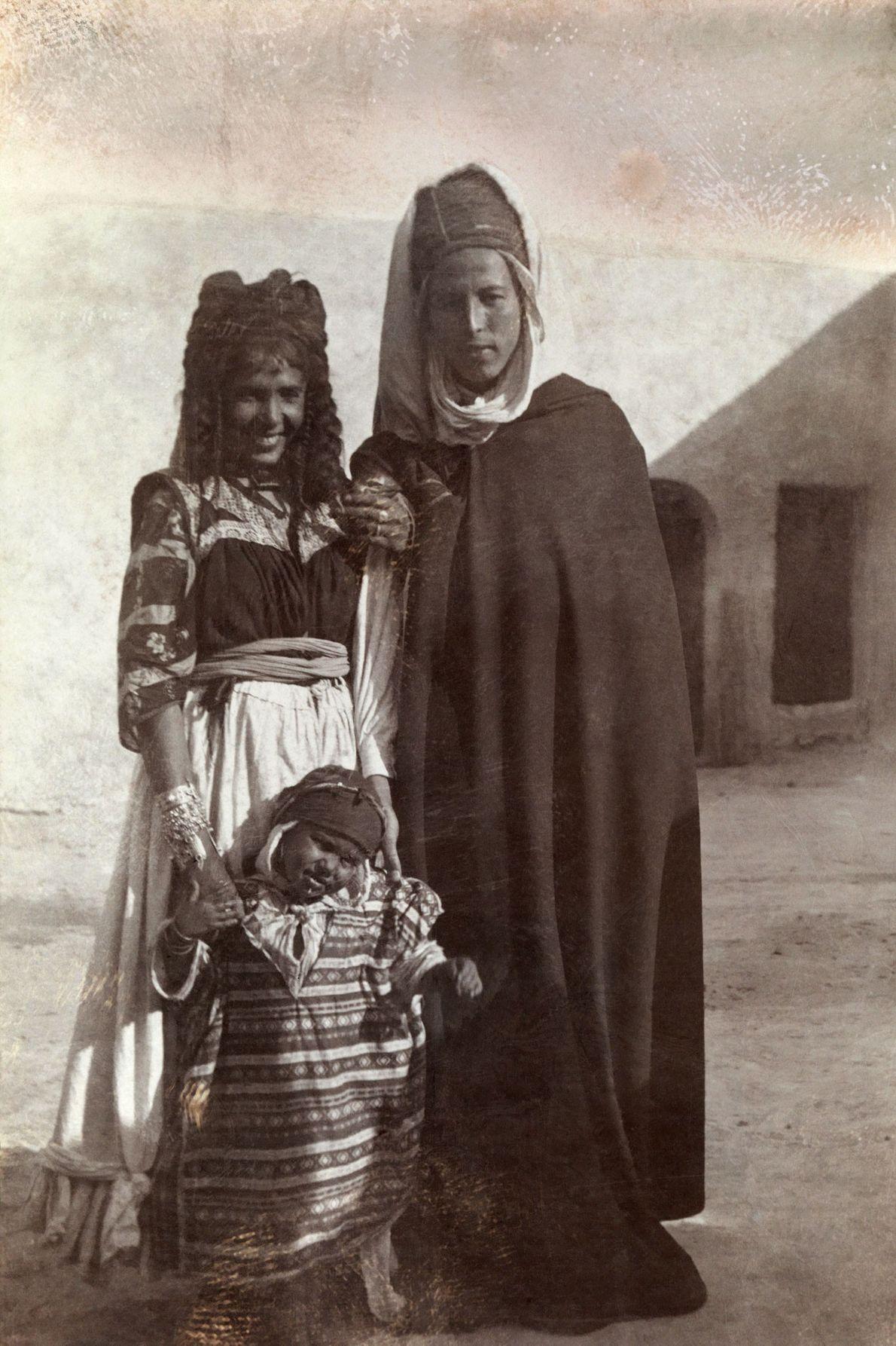 Ein junges algerisches Paar steht mit seinem Kind vor einem Haus in Biskra.