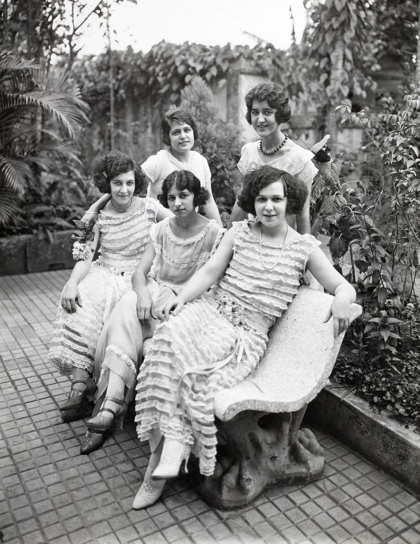 Fünf Spanierinnen in kunstvollen, spitzenbesetzten Kleidern posieren für ein Foto auf einer Bank in der westlichen ...