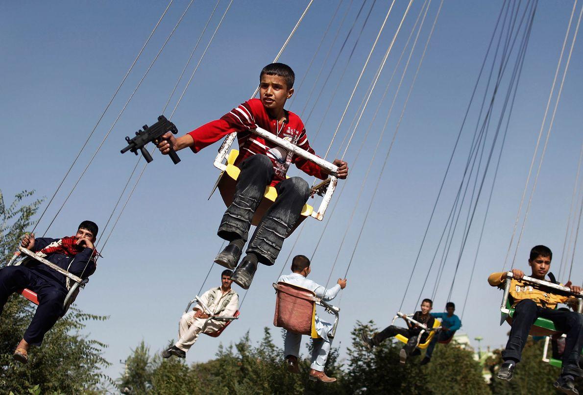 Afghanischer Junge in einem Kettenkarussell